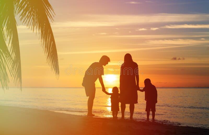 Família feliz com as duas crianças que andam na praia do por do sol imagem de stock
