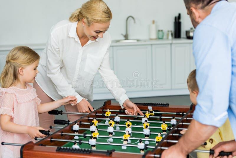 família feliz com as duas crianças que jogam o futebol da tabela junto imagens de stock royalty free