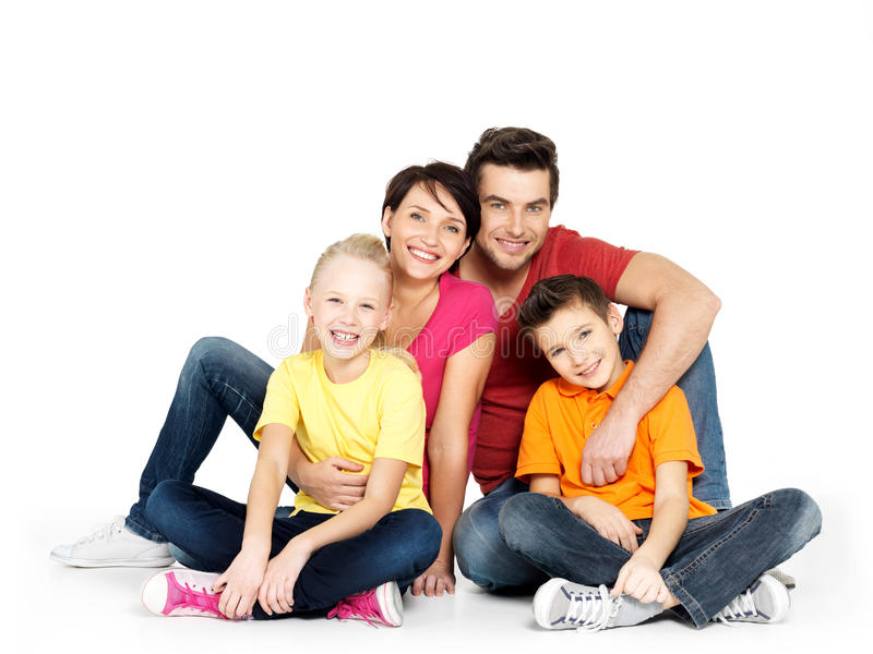 Família feliz com as duas crianças que sentam-se no assoalho branco imagem de stock