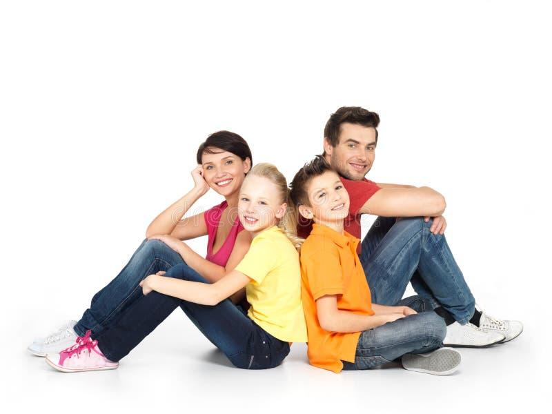 Família feliz com as duas crianças que sentam-se no assoalho branco foto de stock royalty free