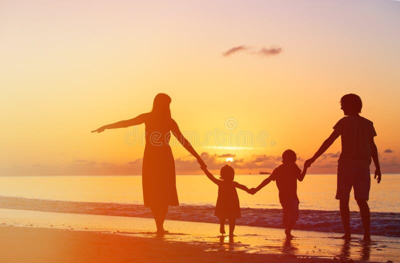 Família feliz com as duas crianças que têm o divertimento no por do sol foto de stock