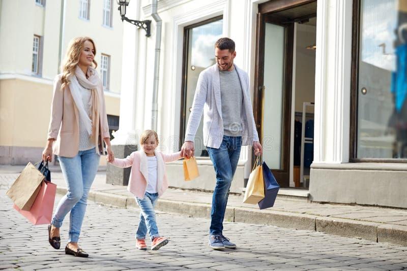 Família feliz com criança e sacos de compras na cidade fotos de stock
