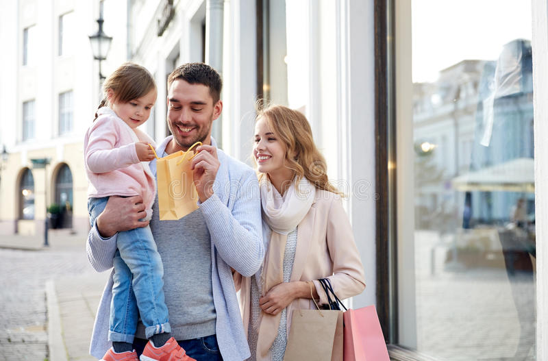 Família feliz com criança e sacos de compras na cidade imagem de stock royalty free