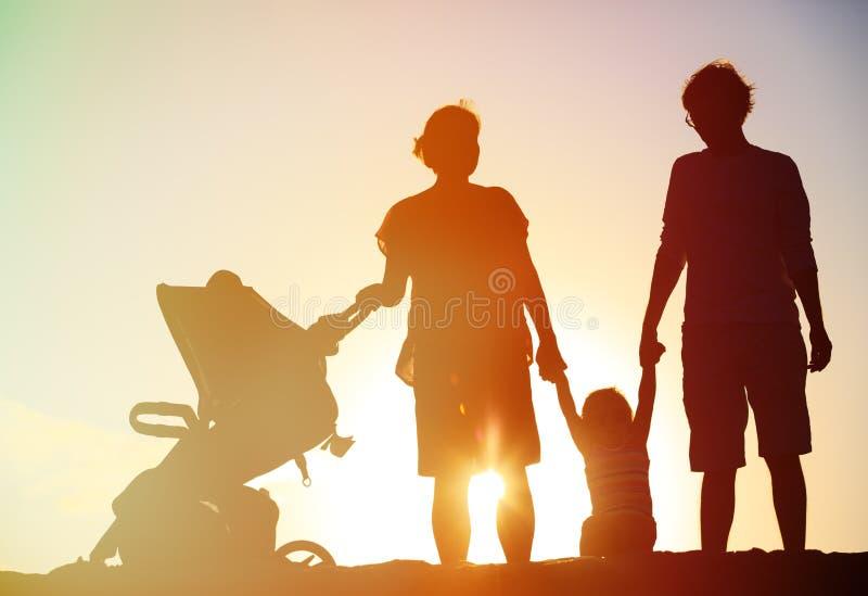 Família feliz com criança junto no por do sol imagens de stock royalty free