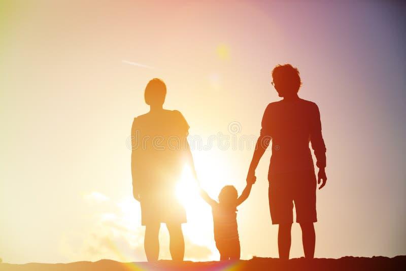 Família feliz com criança junto no por do sol fotografia de stock