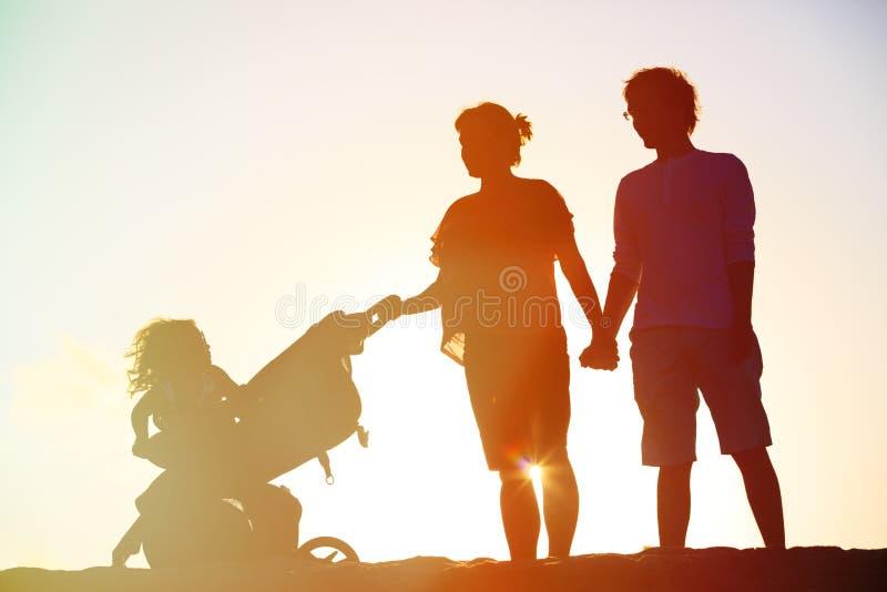 Família feliz com criança junto no por do sol foto de stock royalty free