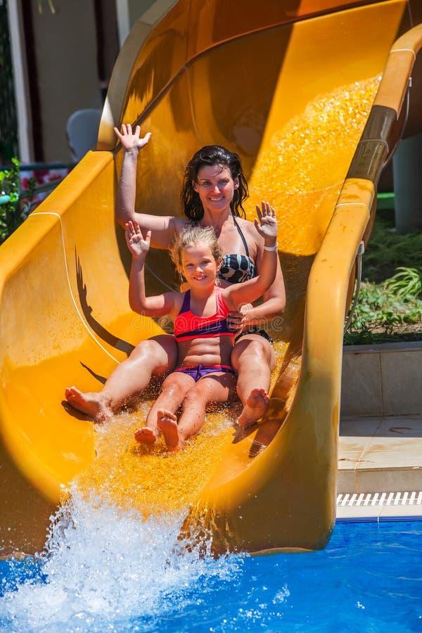 Família feliz com a criança na corrediça de água no aquapark fotos de stock royalty free