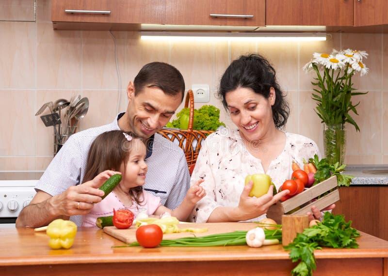 Família feliz com a criança no interior home da cozinha com frutas e legumes frescas, mulher gravida, conceito saudável do alimen fotografia de stock royalty free