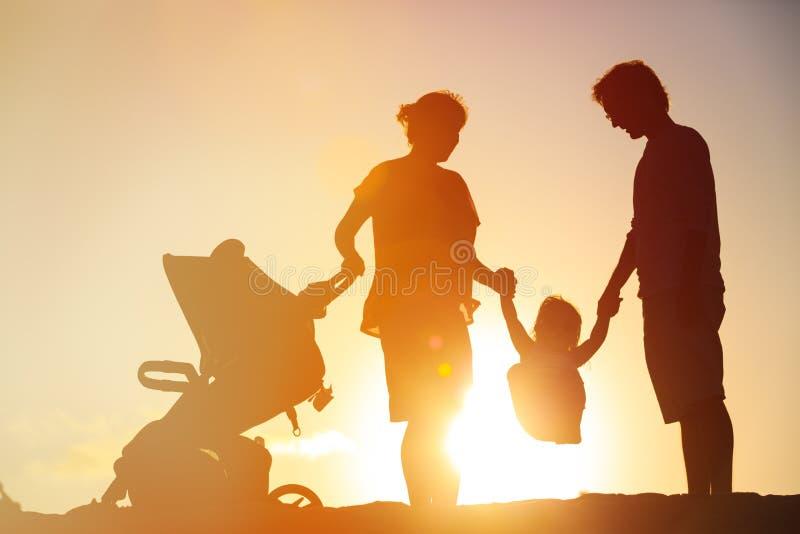 A família feliz com criança pequena e o passeante jogam no por do sol imagem de stock