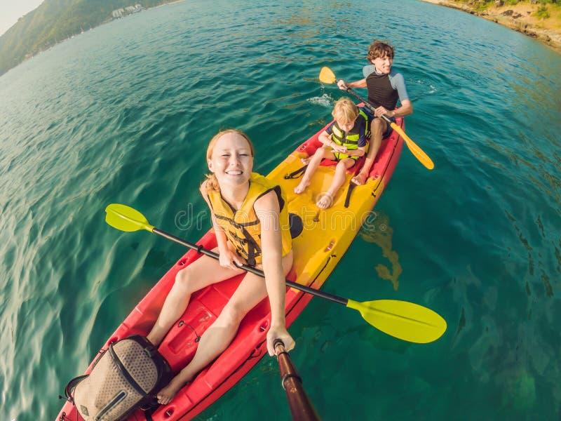 Família feliz com a criança que kayaking no oceano tropical fotos de stock