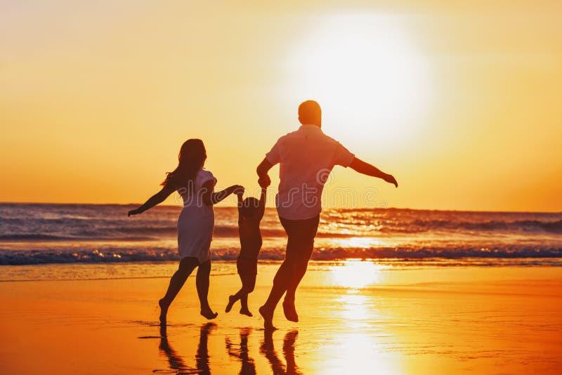 A família feliz com criança tem um divertimento na praia do por do sol imagens de stock