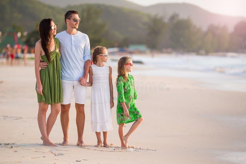 A família feliz com crianças anda na praia foto de stock