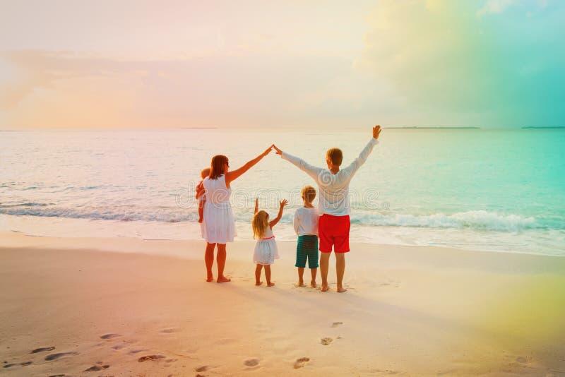 A família feliz com crianças joga, tem o divertimento no por do sol, parenting fotografia de stock