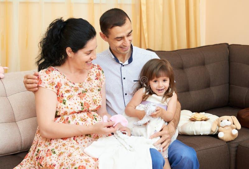 A família feliz com crianças retrato, mulher gravida e homem internos, retrato bonito dos povos senta-se no sofá fotos de stock royalty free