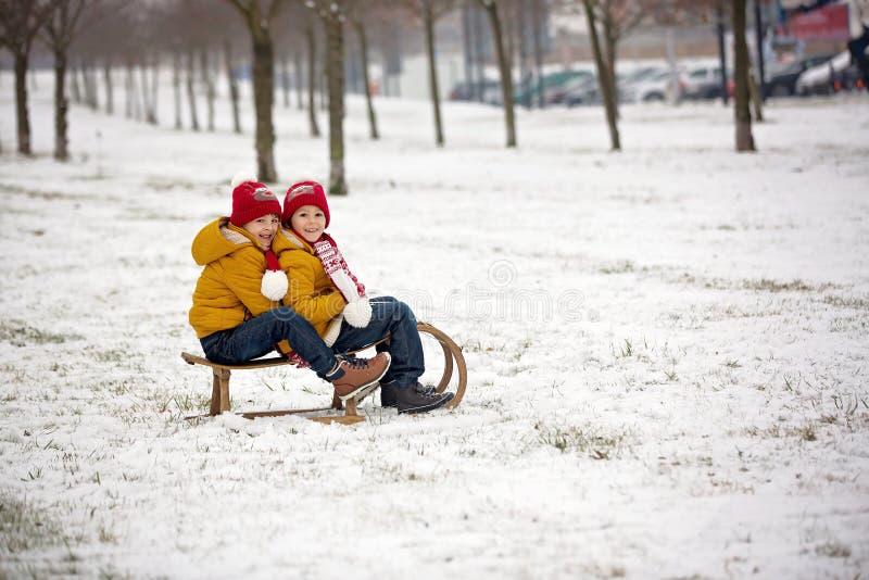 Família feliz com crianças, tendo o divertimento exterior na neve no Natal, jogando com pequeno trenó imagens de stock