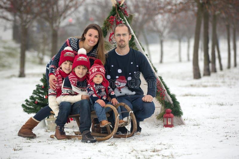 Família feliz com crianças, tendo o divertimento exterior na neve no Natal, jogando com pequeno trenó foto de stock