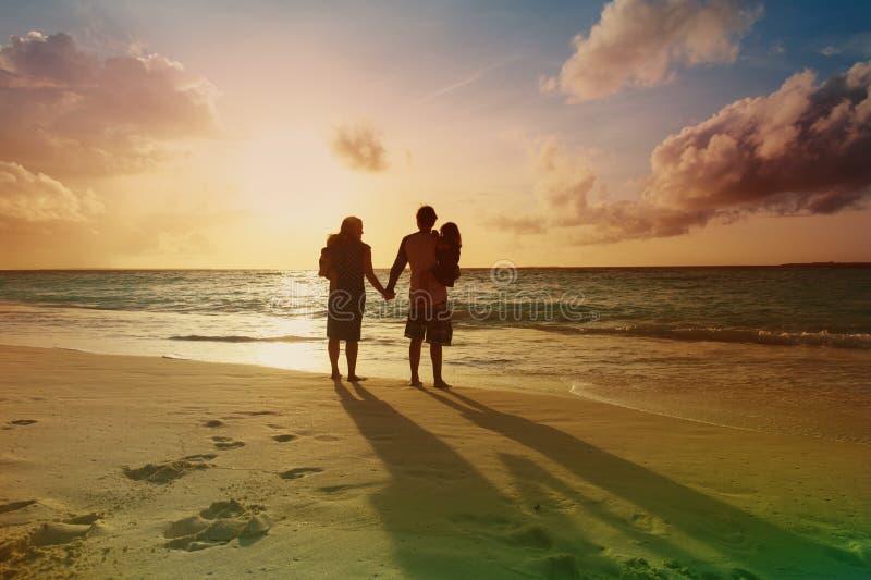 A família feliz com duas crianças anda na praia do por do sol fotos de stock