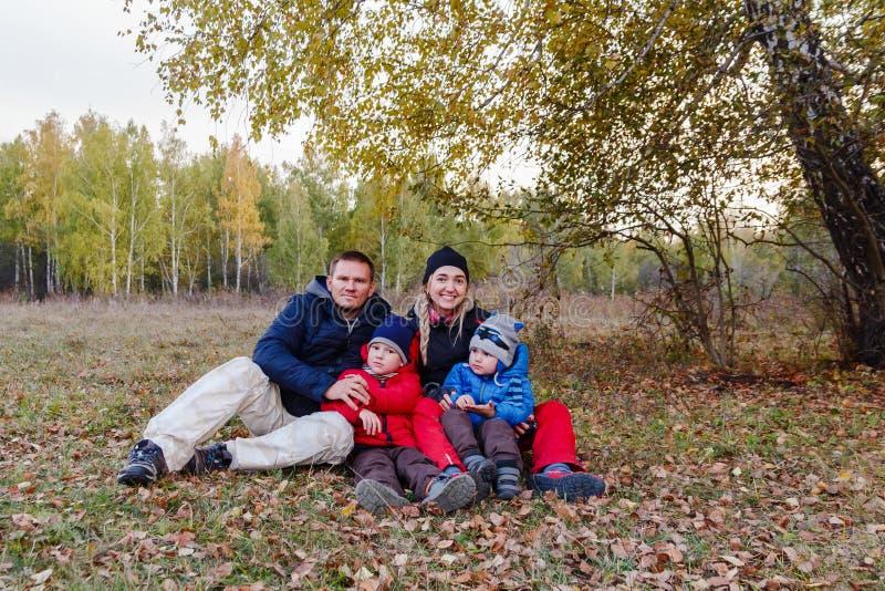 A família feliz com duas crianças senta-se na floresta do outono imagens de stock royalty free