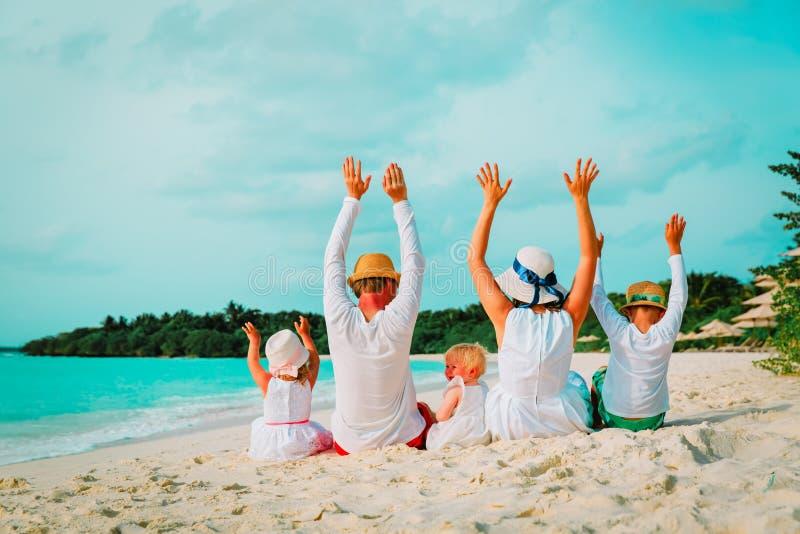 Família feliz com duas mãos das crianças acima na praia imagens de stock