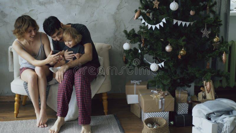 Família feliz com a filha pequena bonito que senta-se perto da árvore de Natal e que usa o smartphone em casa fotos de stock