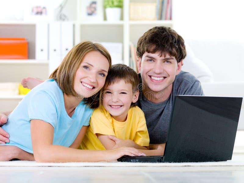 Família feliz com filho em casa com portátil imagens de stock royalty free