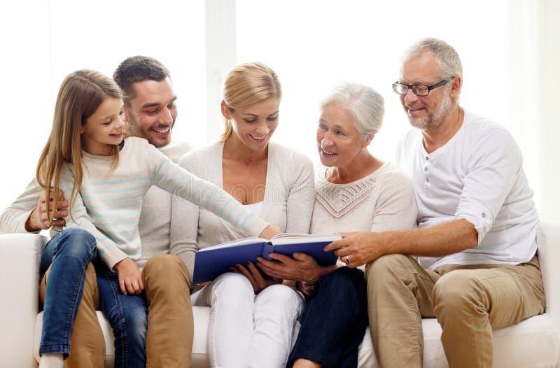 Família feliz com livro ou álbum de fotografias em casa imagens de stock royalty free