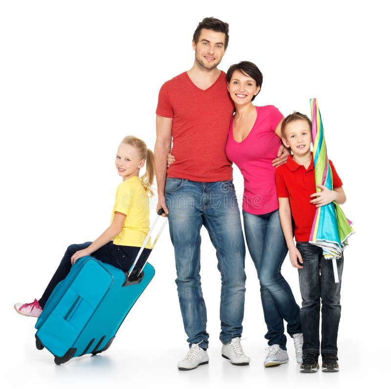 Família feliz com a mala de viagem no estúdio imagem de stock royalty free