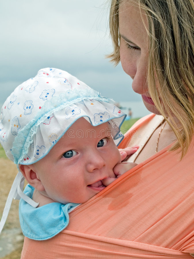 Família feliz com matriz e bebê no estilingue imagem de stock royalty free