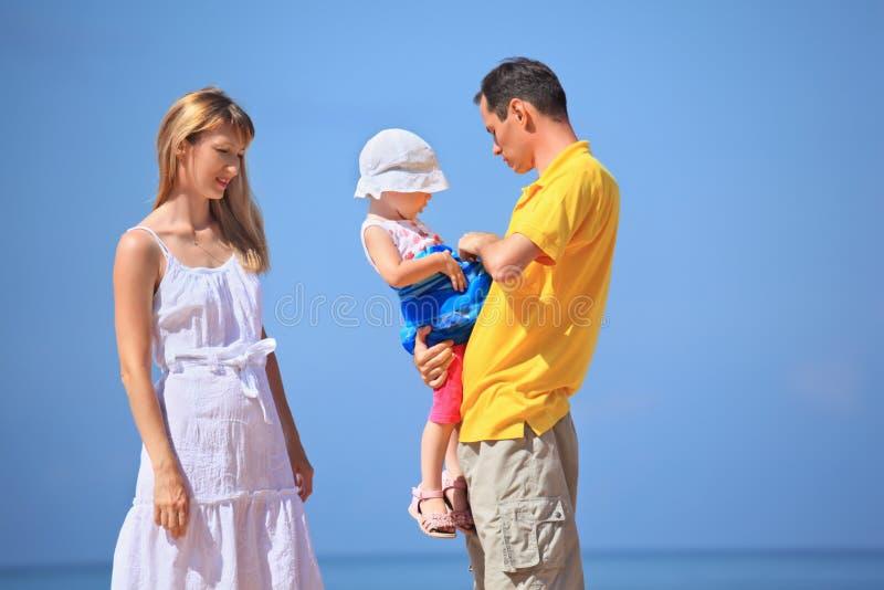 Família feliz com a menina de encontro ao mar foto de stock