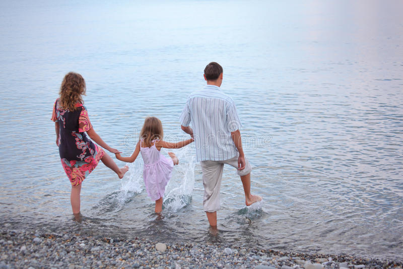A família feliz com a menina na praia vai na água foto de stock royalty free