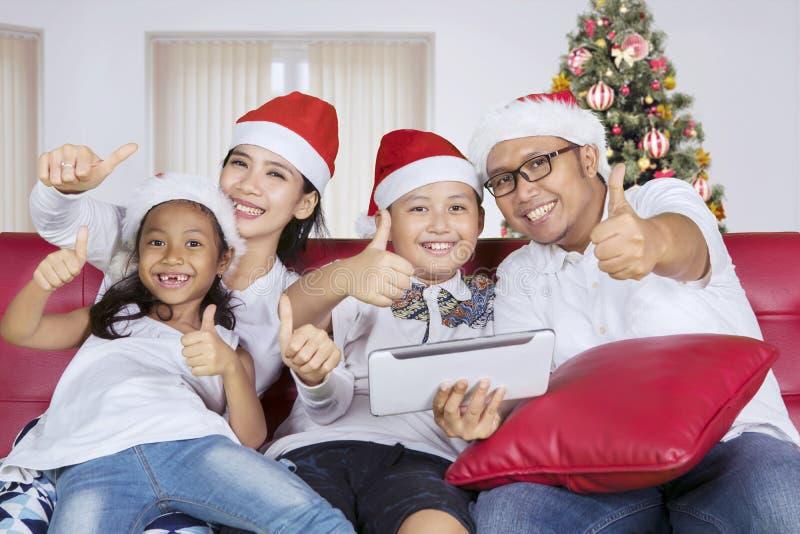 A família feliz com mostra do chapéu de Santa manuseia acima foto de stock