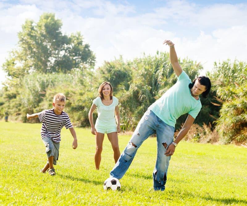 Família feliz com o adolescente que joga no futebol imagens de stock