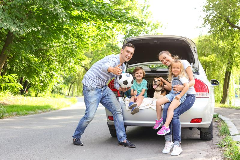 Família feliz com o cão bonito perto do carro fora imagens de stock royalty free