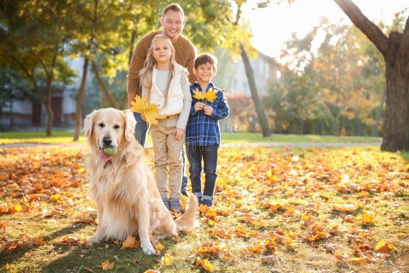 Família feliz com o cão no parque do outono imagens de stock royalty free