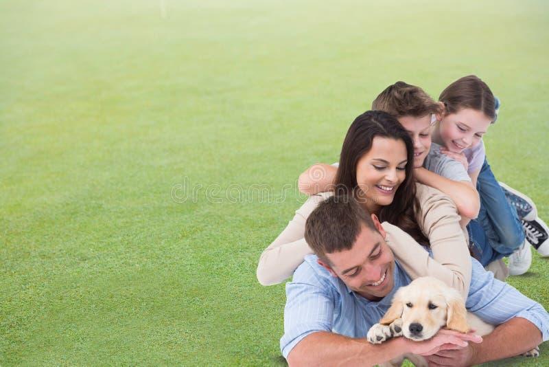 Família feliz com o cão que encontra-se na grama foto de stock