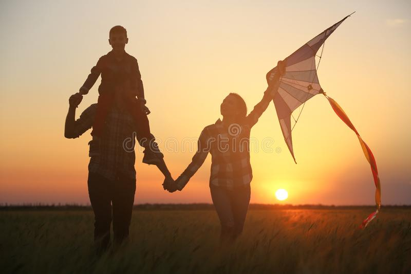 Família feliz com o papagaio no campo no por do sol imagem de stock royalty free
