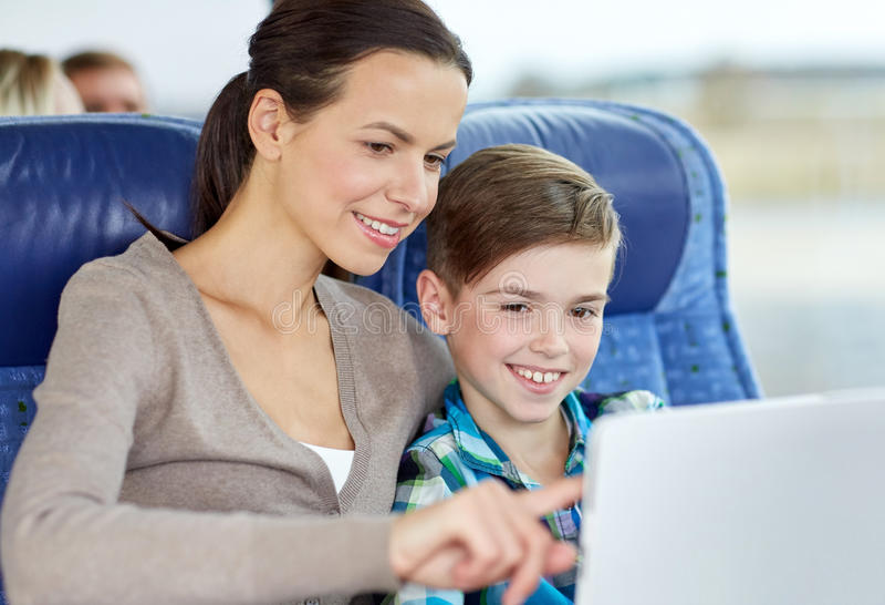 Família feliz com o PC da tabuleta que senta-se no ônibus do curso imagens de stock
