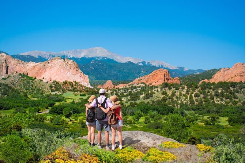 Família feliz com os braços em torno de se que aprecia o Mountain View bonito em caminhar a viagem imagens de stock royalty free