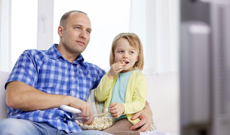 Família feliz com pipoca que olha a tevê em casa imagens de stock