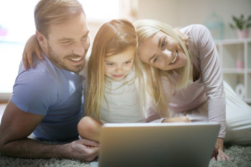 Família feliz com portátil em casa imagem de stock