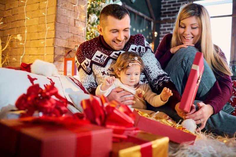 Família feliz com um bebê em uma sala do Natal foto de stock royalty free