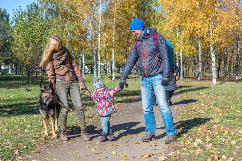 A família feliz com um cão está andando imagem de stock royalty free