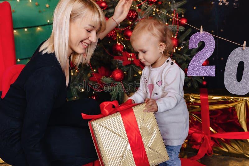 A família feliz com uma criança comemora o ano novo perto da árvore de Natal imagens de stock