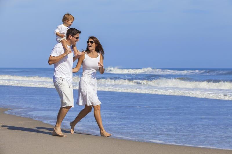 Família feliz da criança da mulher do homem que joga na praia foto de stock royalty free