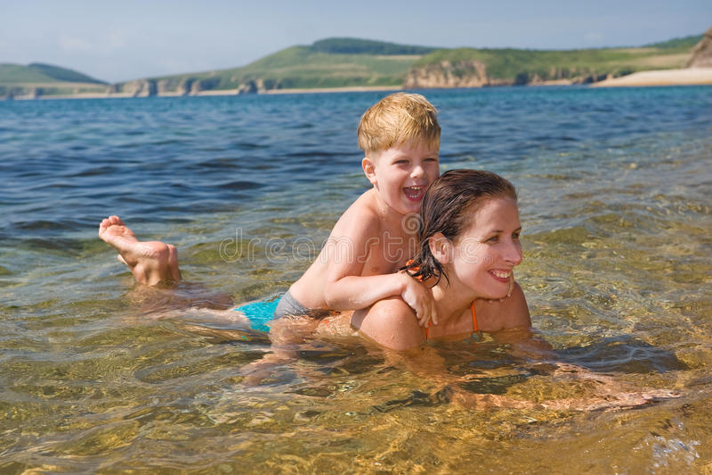 Família feliz da mãe com a criança que joga nas ondas foto de stock royalty free