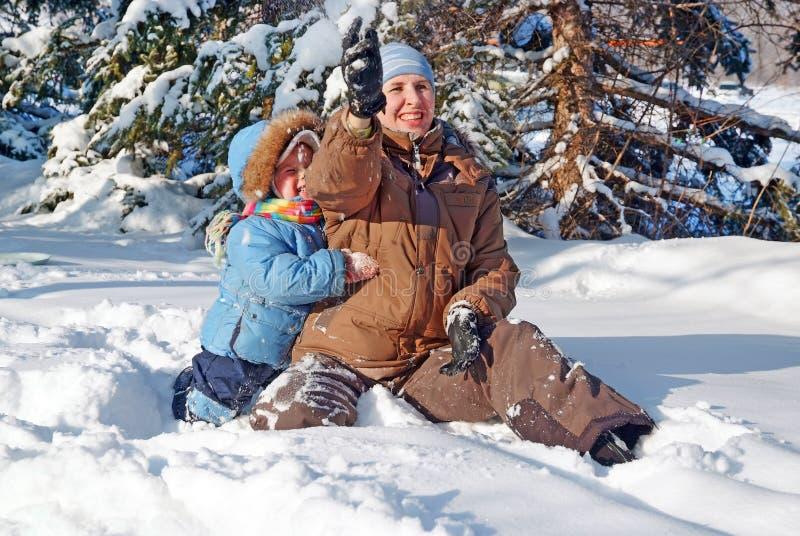 Família feliz da mãe com a criança que joga no parque do inverno imagem de stock