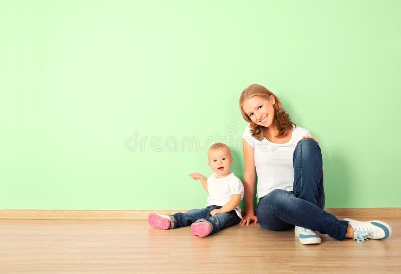 Família feliz da mãe e da criança que sentam-se no assoalho em um empt foto de stock royalty free