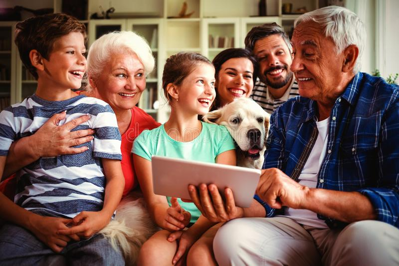 Família feliz da multi-geração que usa a tabuleta digital na sala de visitas imagens de stock