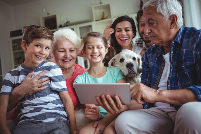Família feliz da multi-geração que usa a tabuleta digital na sala de visitas fotografia de stock royalty free