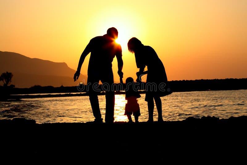 Família feliz da silhueta três de jogo fotos de stock royalty free